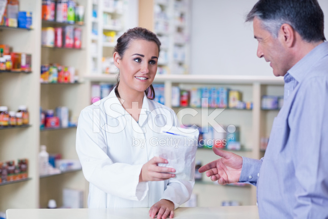 Trainee Giving Bag of Pills TO A Customer Stock Photos - FreeImages.com