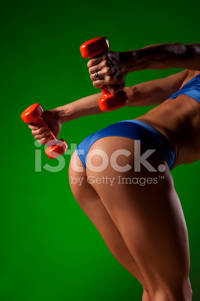 Female Muscular Arms With Weights And Buttocks On Green Stock Photos