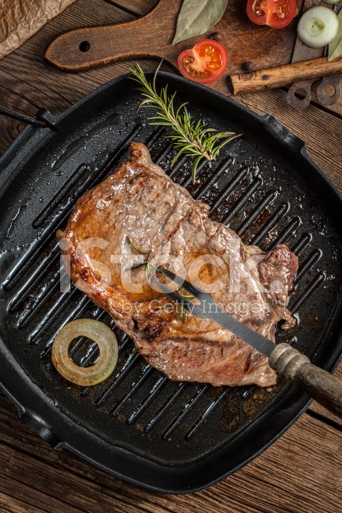 Стейк из говядины с розмарином на сковороде