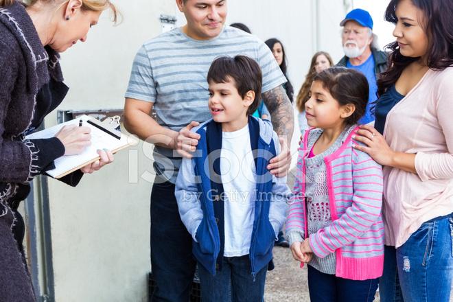 Young Hispanic Family Signing UP TO Volunteer AT Food Bank