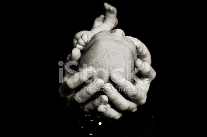 Portrait of hands holding newborn baby on black background