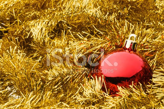 Red christmas ball over gold tinsel garland stock photos