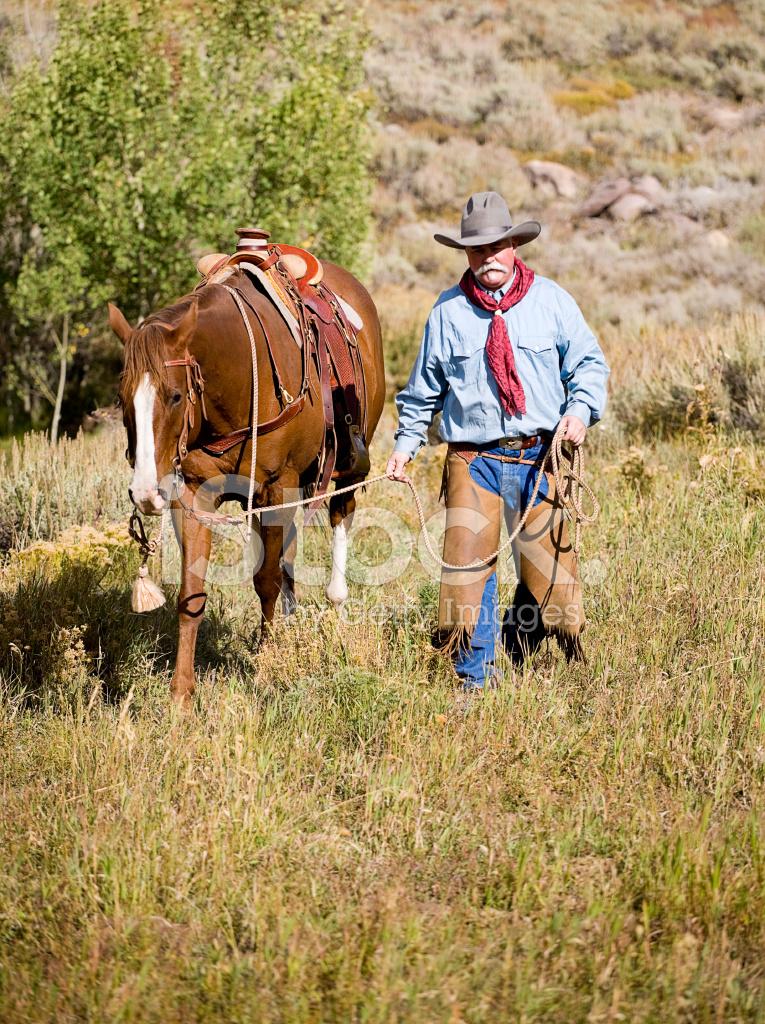 Cowboy Walking With His Horse Stock Photos