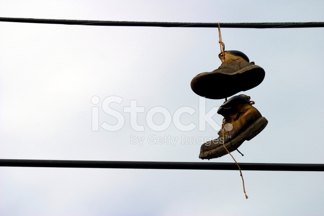Shoes hanging from a telephone wire stock photos for Hang photos from wire
