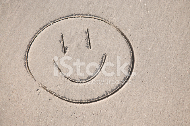 Simple Smiley Face Drawn In Sand On The Beach Stock Photos