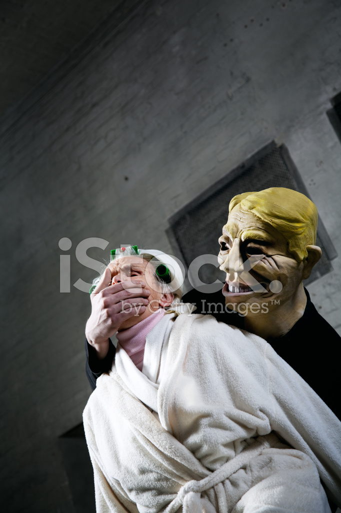 Man Wearing Mask Kidnapping Senior Woman stock photos