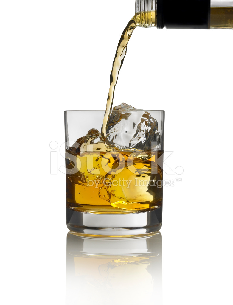gold liquor pouring into glass with ice on white background stock