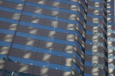 modern office building facade with relected sunlight stock photos