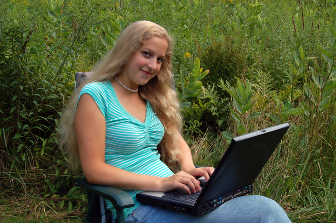 Student with computer outdoors