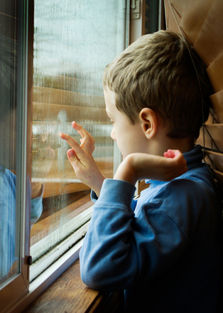 Boy writing in window fog