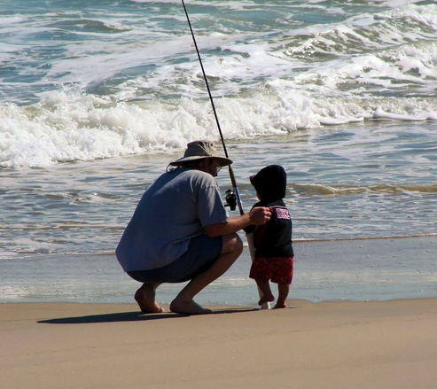 otec s malým dítětem s prutem na břehu moře (otcovská rada)