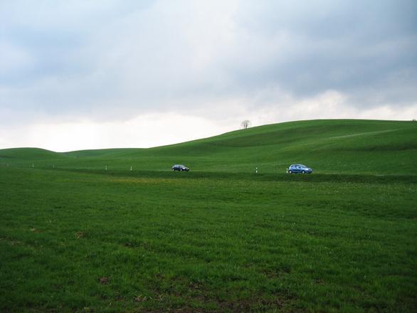 Blue car in green landscape