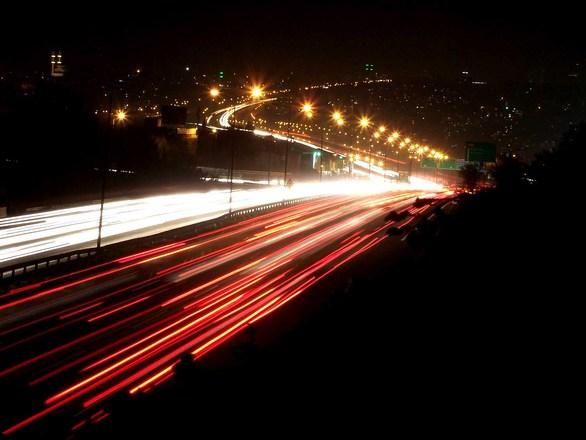 טראפיק - הפושטק - בתמונה רואים צילום של כביש בלילה עם אורות ופנסים אפקט מרהיב