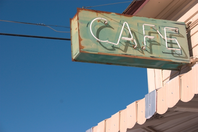 Rusted neon green and white cafe sign