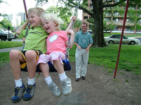 Family time in the park: Siblings swinging