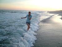 Dievča kráča po pláži vo vlnách mora - tancovanie vo vlnách - vlny na pláži - užívanie si života - radosť z maličkostí