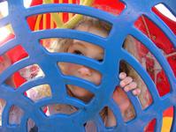 Girl Peeking Through Play Equipment
