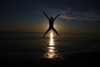 Skok nad vodou pri zapadajúcom slnku - skok nad vodou s roztiahnutými rukami a nohami