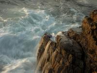 Ola rompiendo en las rocas