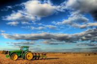 Zelený traktor so žltými kolesami na poli pod modrou oblohou s bielymi oblakmi
