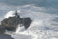 Rybár chytá ryby na rozbúrenom mori - muž sedí na skale s udicou v ruke a v mori sú veľké vlny