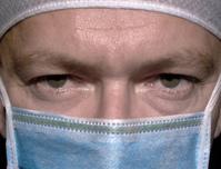 Chirurg - lekár s rúškom na tvári - muž má rúšok a lekársku čiapku