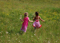 Little girls running in field