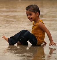Detská radosť - smejúci sa chlapec sedí v daždi na zemi
