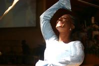 Usmiata žena v bielom dvíha pravú ruku hore - šťastná žena tancuje