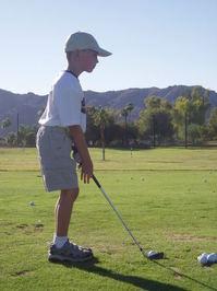 Boy hitting golf balls 2