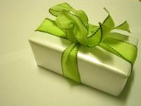Darček zabalený v bielom papieri previazaný zelenou stuhou