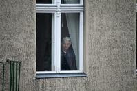 old sad woman looking through window