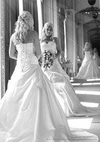 Pripravená nevesta v svadobných šatách, s kyticou v ruke a so svadobným účesom sa na seba pozerá do zrkadla - nevesta čakajúca na svadbu