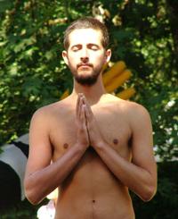 Muž so zatvorenými očami medituje v lese - muž má späté ruky v modlitbe - muž sa modlí