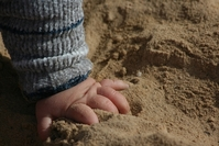 Baby hand in sand