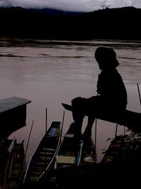 boy sitting at river