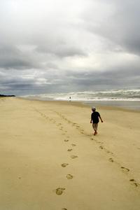 Osamelý človek na pláži pri mori - dvojité stopy v piesku na pláži - nikdy nie si sám