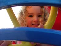 Child Peeking through play equipment