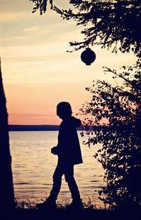 Little boy walking by a lantern