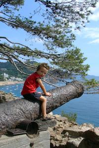 boy sitting on a canon a Tossa de Mar