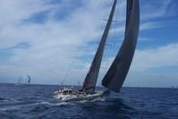 A vessel sailing into the ocean in a regatta