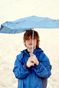 Boy with broken umbrella